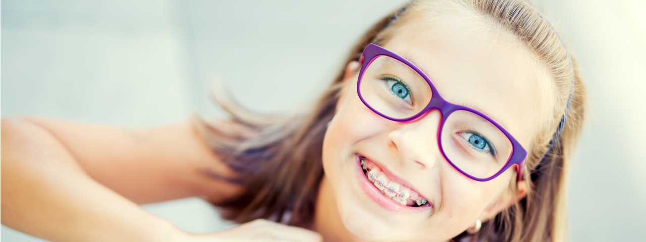 Young child with braces and glasses